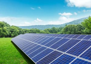 Solar panels and mountains in green field